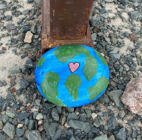 The earth painted on a rock, along with a heart, as a reminder it's Earth Day