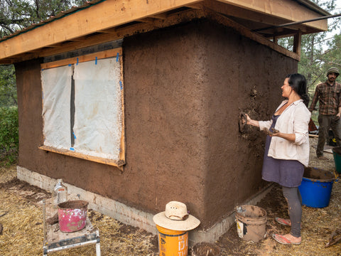 Mud plastering a straw bale building