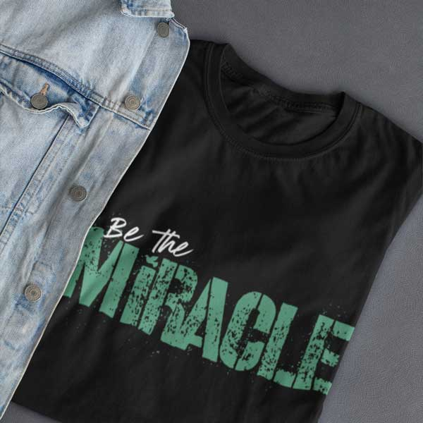Flat lay of a black BE THE MIRACLE Christian t-shirt from Glor-e