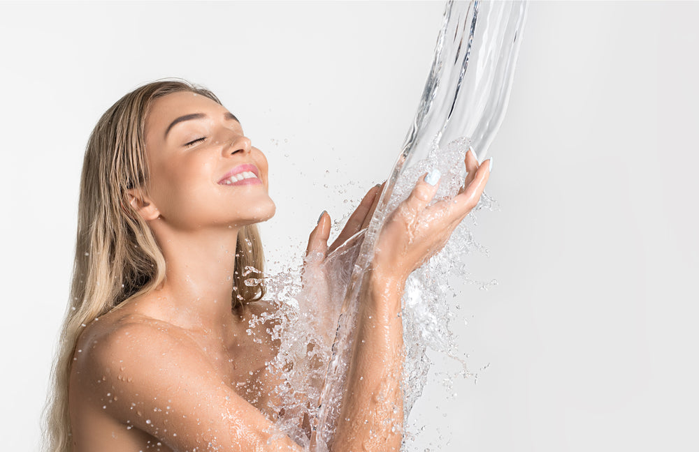 Cold shower benefits, beautiful womans standing under a shower with water raining down on her while she smiles with eyes closed