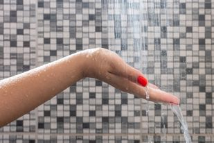 Woman holding out hand with red painted nails inside tiled shower stall with water spraying down on it