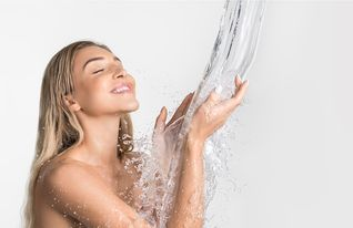 Woman under shower head getting rained on by water showering