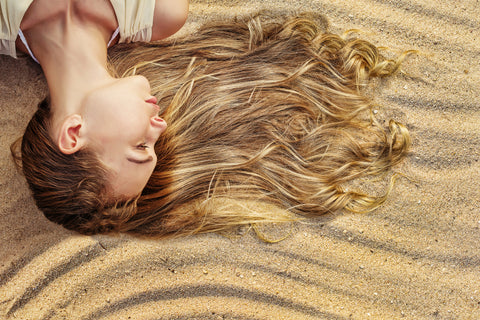 Beautiful woman laying on sandy dunes with wavy golden hair flowing