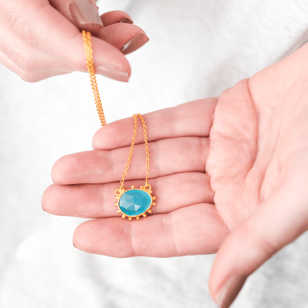 detailed gold necklace with blue stone