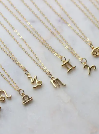 A dainty little zodiac symbol necklace in gold