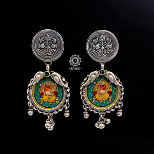Silver Earring with an intricate miniature hand painted Ganesha Motif in vibrant colours. Enclosed with a glass top, these are hand painted one of a kind wearable art pieces.