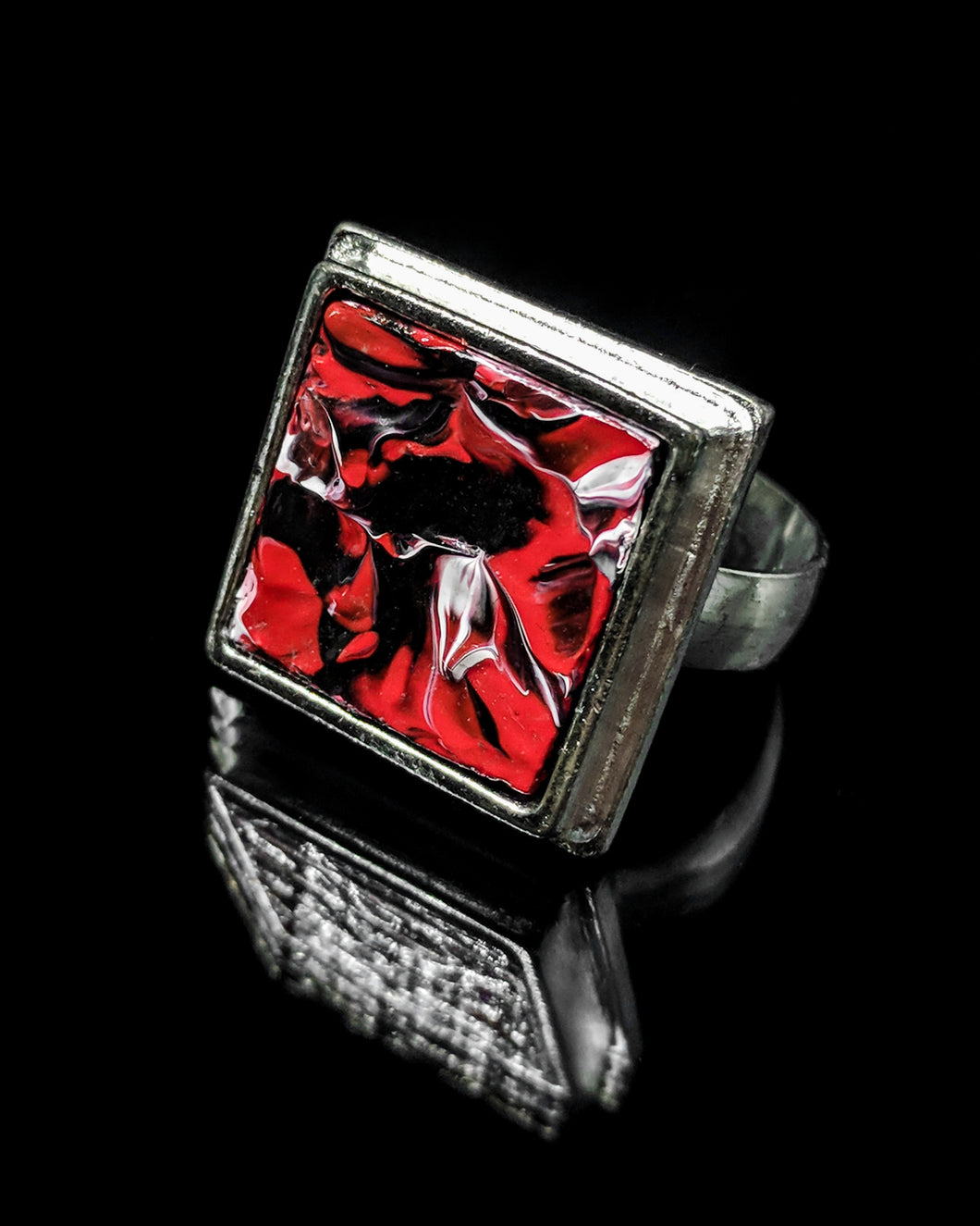 The front of this painted ring has strong red shapes, and black and white accents.