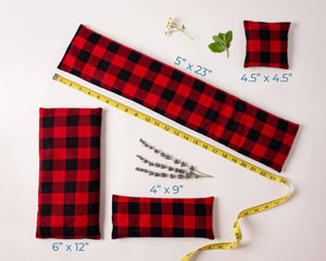 4 Whiffy Bean Bags, which are microwave heating pads/ice packs laid out to show the different sizes. Fabric is read and black buffalo plaid flannel fabric.