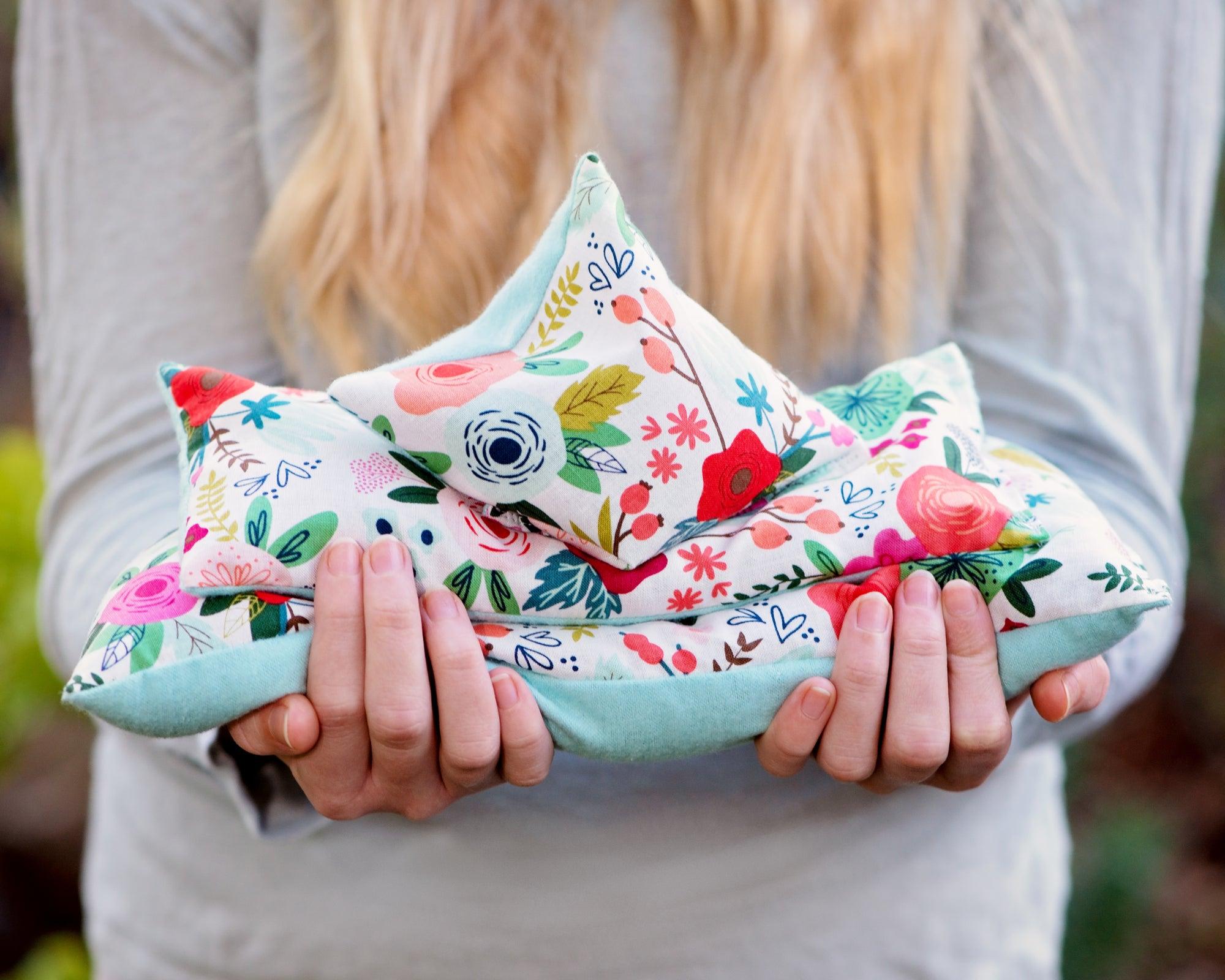 Girl holding microwave heating pads and or ice packs in her hands.