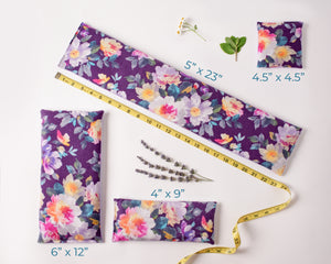 4 warm compresses/cold compresses laid out to show the different sizes. Fabric is purple watercolor floral flannel.