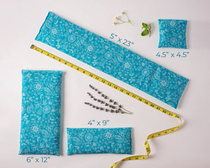 4 microwave heating pads/ice packs laid out to show the different sizes. Fabric is rustic blue