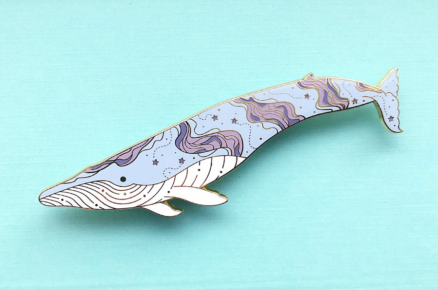 Large blue whale enamel pin with nebula and stars design along its body