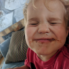 Little boy smiling with his eyes closed with cookie crumbs acrossed his face
