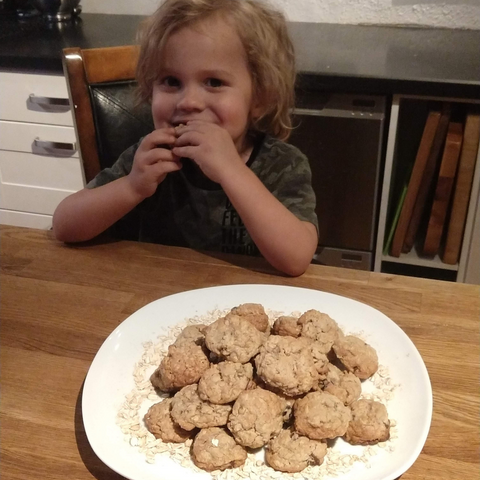 Adorable boy eating oatmeal cookies