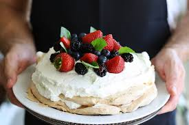 hands holding a cake and berries