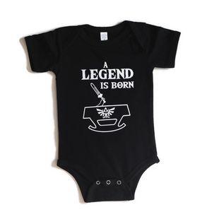 Black infant one piece with white imate of baby hand coming out of cradle with sword