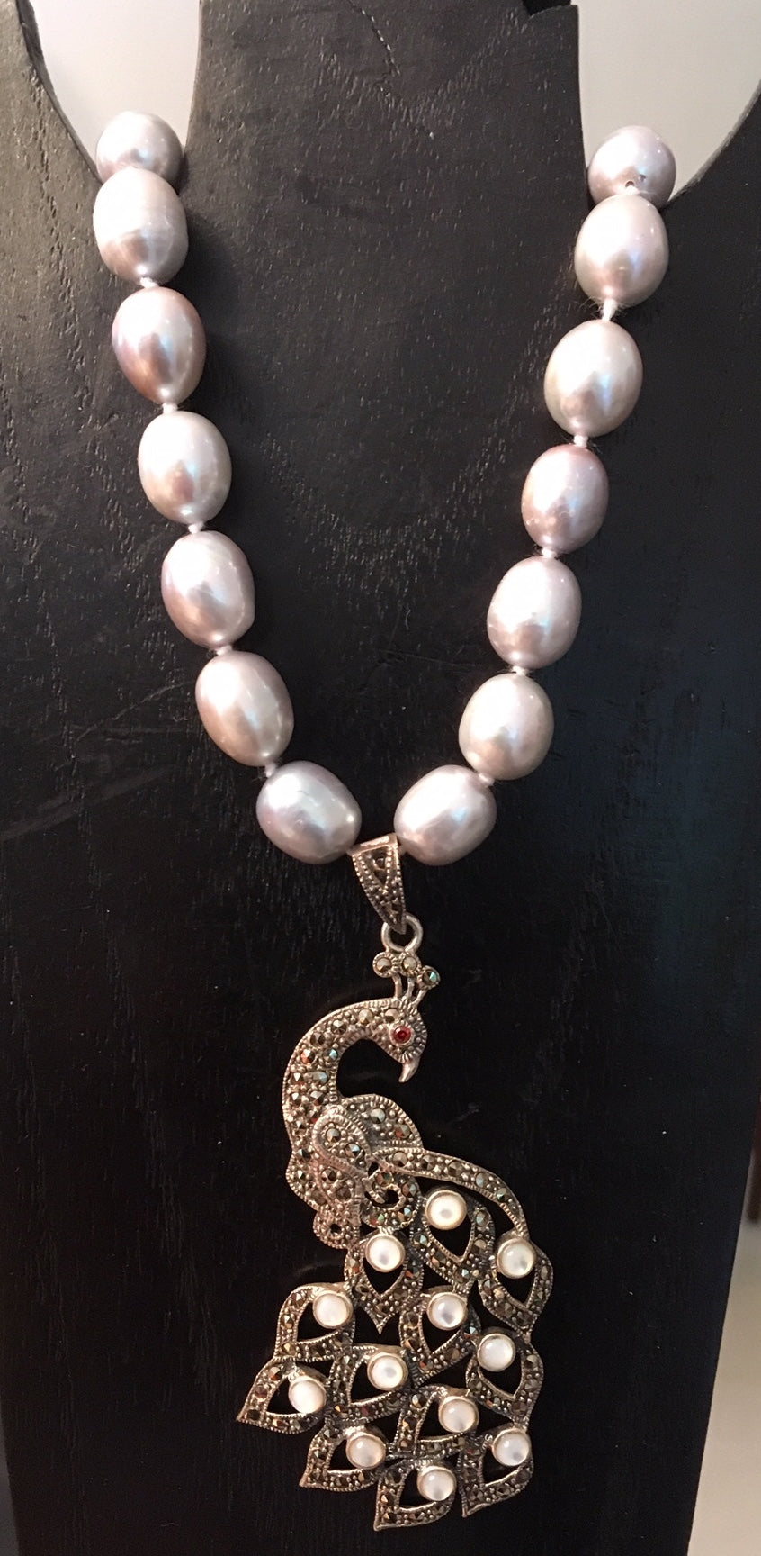 Cultured pearls with a large marcasite peacock pendant
