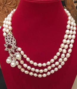 Three strand white pearls with large crystal charm