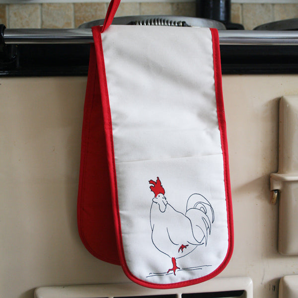 oven gloves with a rooster design and red underside on an aga