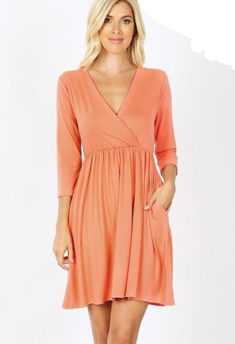 Coral Dress with 3/4 length sleeve and a cross over front V. Elastic waist with pockets and knee length.