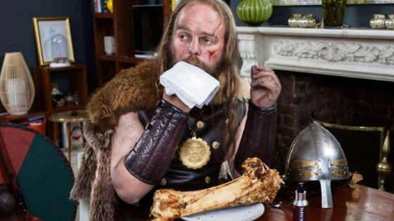 viking eating a piece of meat with bone inside a modern urban room