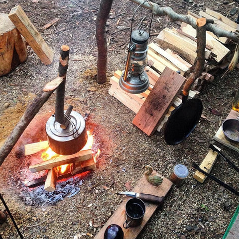 bushcraft and survivalist camp with fire and cooking equipment