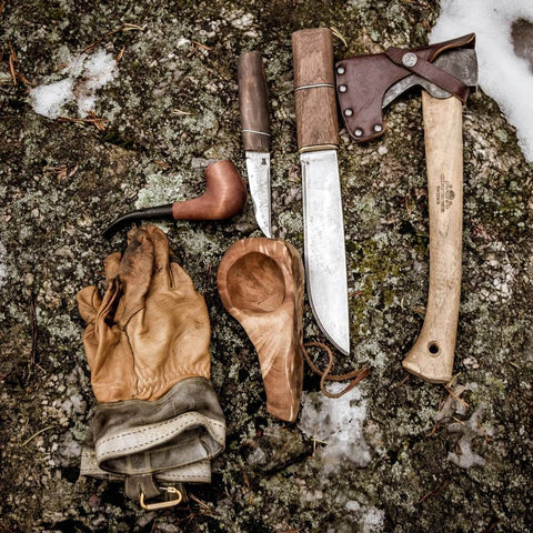 axe knife spoon in wood and gloves equipment for bushcraft and outdoor wild camping