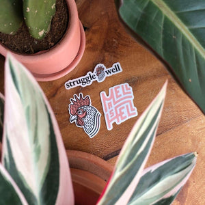 The combination of all three Mellow Rooster brand stickers on a wooden table with plants on defocused the foreground
