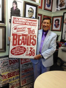 Tony Booth holding one of his Beatles concert posters