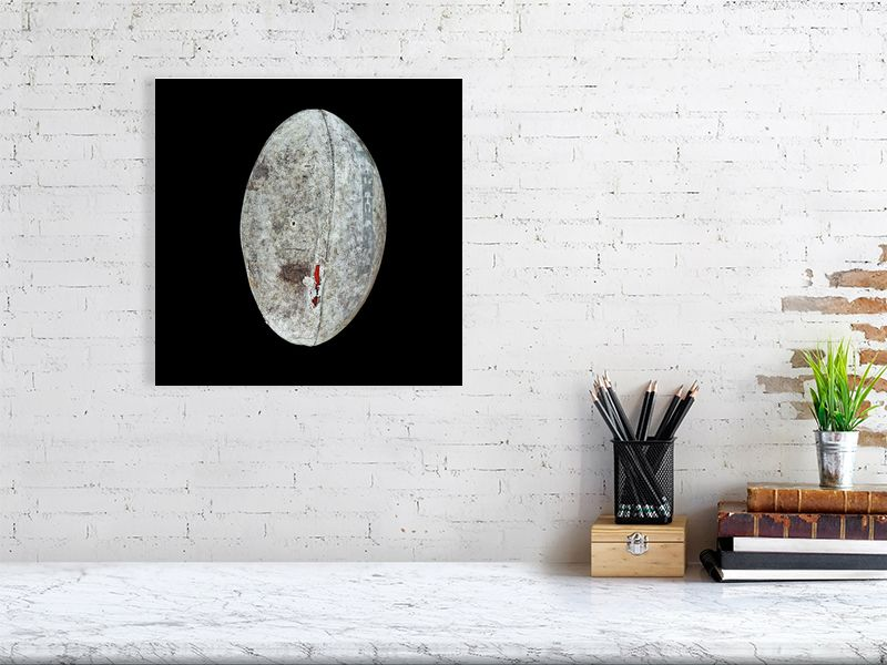 Grey rugby ball on black background print above desk