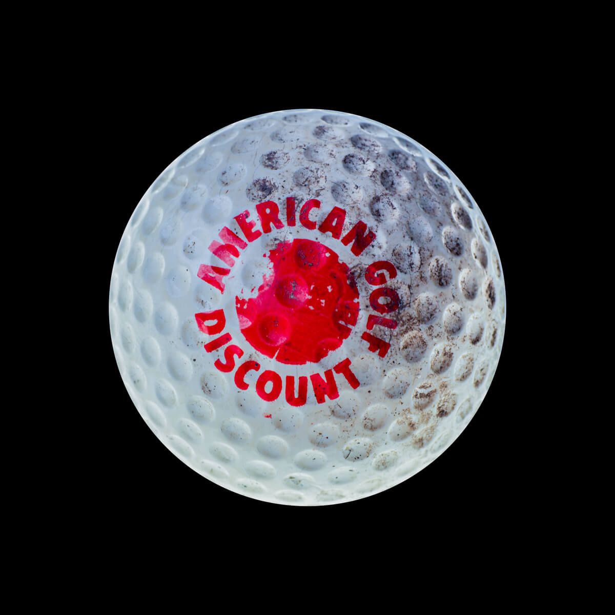 "White golf ball that says ""American golf discount"" in red"