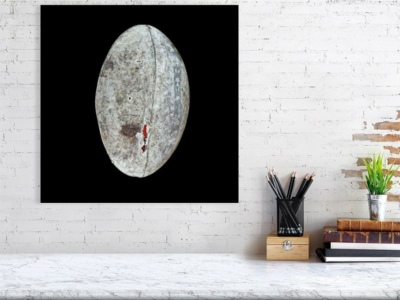 Large grey rugby ball on black background print above desk