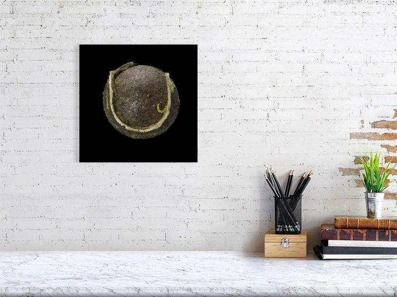 Brown tennis ball on black background print above desk