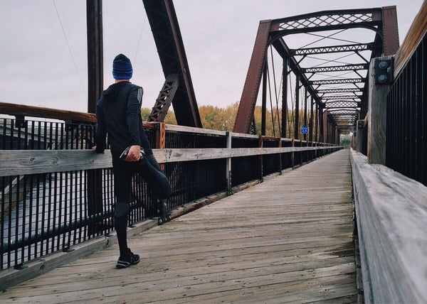 man-stretching-before-jog-on-a-bridge