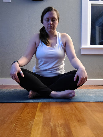 Woman sitting on yoga mat with eyes closed