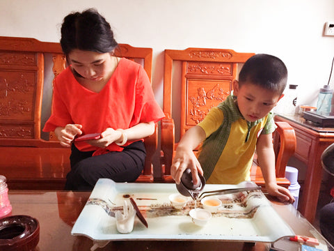 A grandson brews from his grandfather's gongfu set up, the student becomes the master