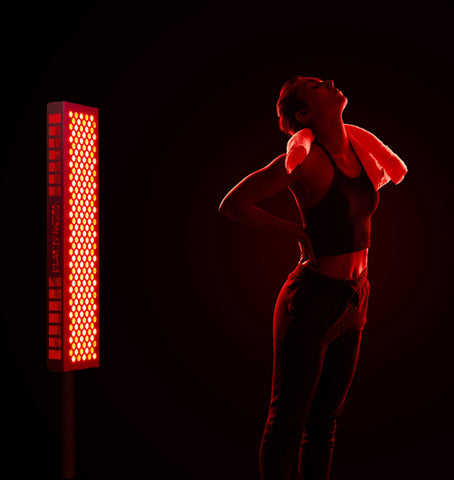woman treating low back pain with red light therapy device