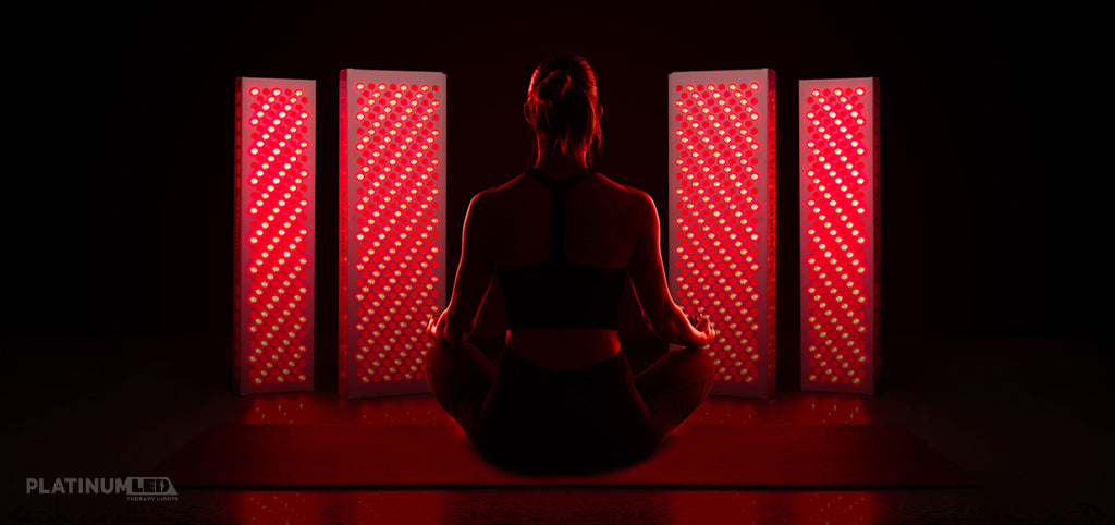 woman sitting in front of red light therapy devices