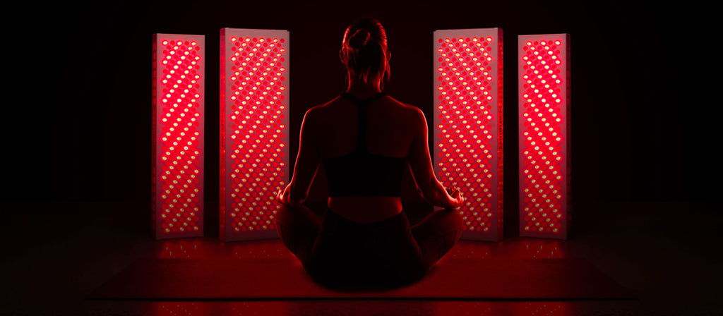 woman meditating in front of red light therapy devices
