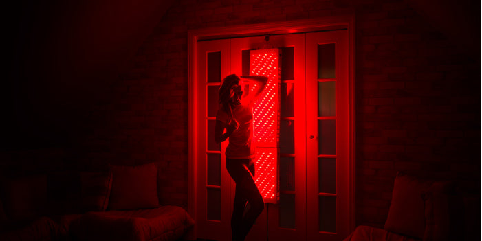 woman using red light therapy at home