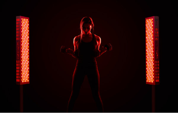 Woman in Active Wear Standing Next to Red Light Therapy Devices