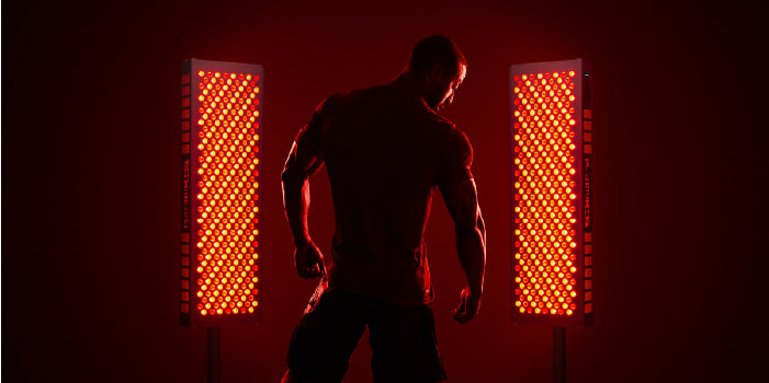 Body Builder Standing Next to Red Light Therapy Device