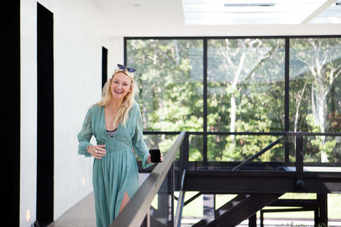 Smiling blonde woman in a house with tall windows