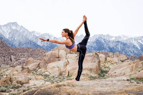 Woman doing yoga against a rocky, mountainous background