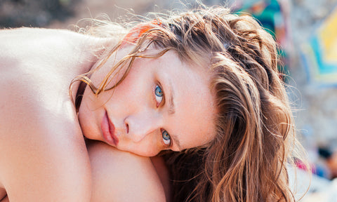 Blue-eyed woman on the beach with wet hair