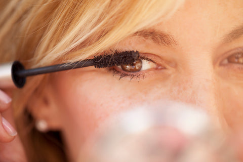 Blonde woman applying mascara to eyelashes