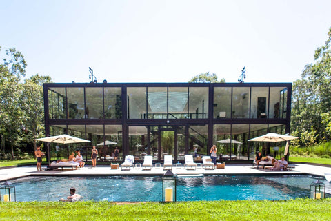 Glass house with tall windows overlooking a pool party