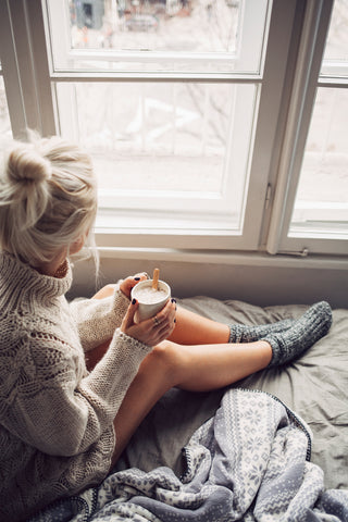 Cozy blonde woman in a chunky sweater gazing out window with hair in bun