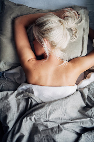 Beautiful Blonde Woman Laying in Bed with a Loose Bun