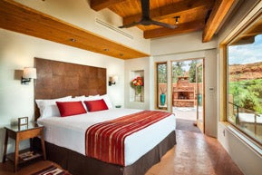 Desert-inspired bedroom with exposed wood and red accents